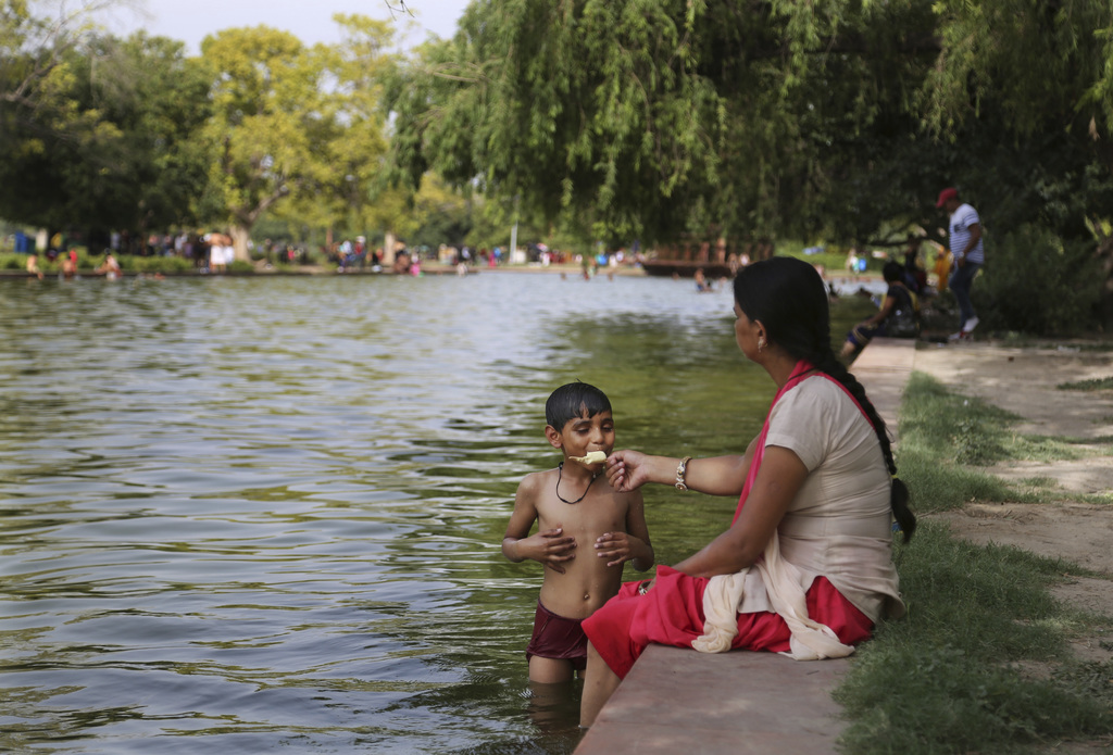 An Indian woman offers an ice-cream to her son as he cools off in a pond near the India Gate monument on a hot day in New Delhi, India,...