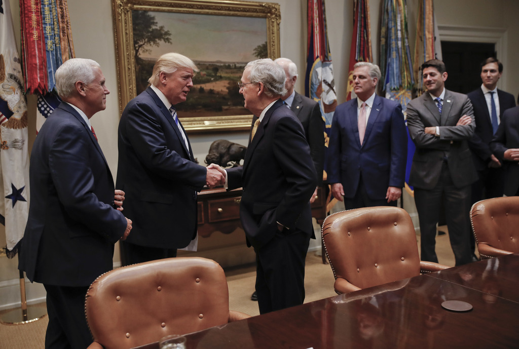 President Donald Trump shakes hands with Senate Majority Leader Mitch McConnell of Ky., center, before the start of a meeting with Hous...