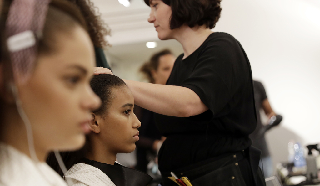 Models get her hair done in the backstage prior to the presentation of the Versace men's Spring-Summer 2018 collection, part of the Mil...
