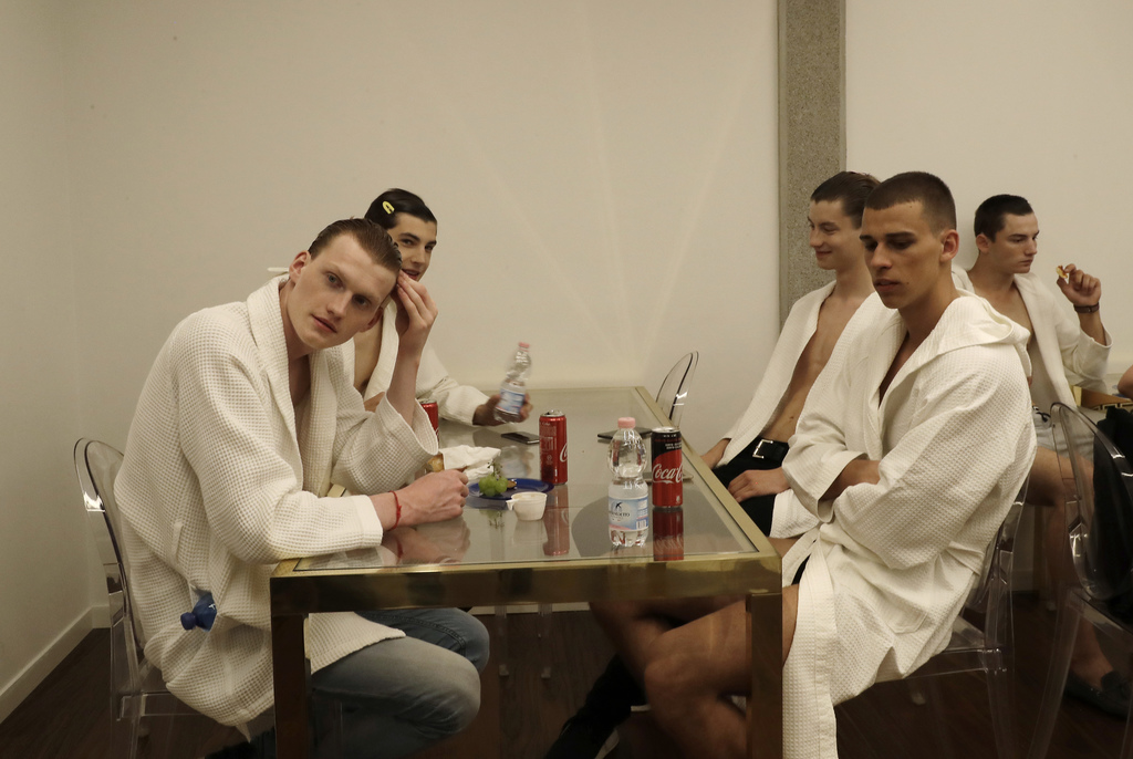 Models have a break in the backstage prior to the presentation of the Versace men's Spring-Summer 2018 collection, part of the Milan Fa...