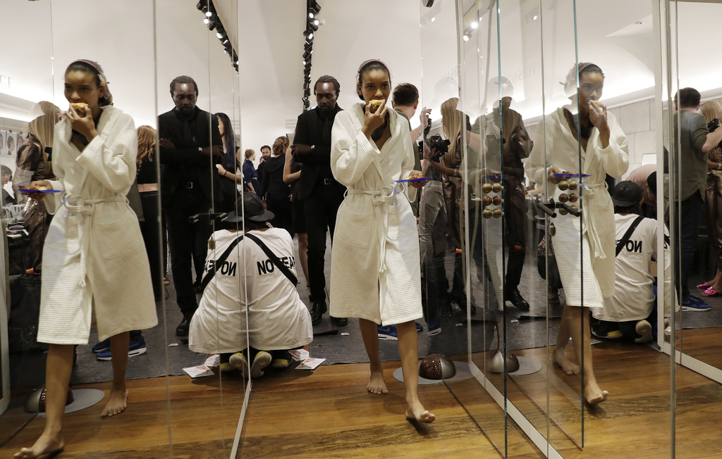 A model is reflected in mirrors as she walks in the backstage prior to the presentation of the Versace men's Spring-Summer 2018 collect...