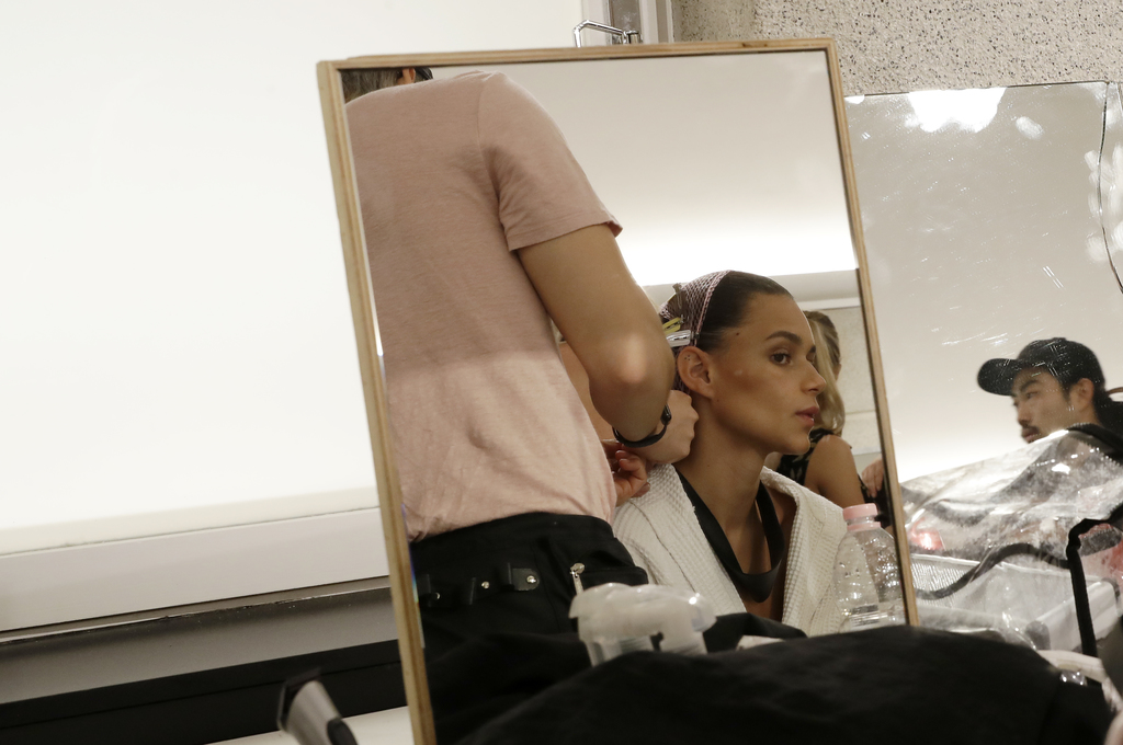 Models gets her hair done in the backstage prior to the presentation of the Versace men's Spring-Summer 2018 collection, part of the Mi...