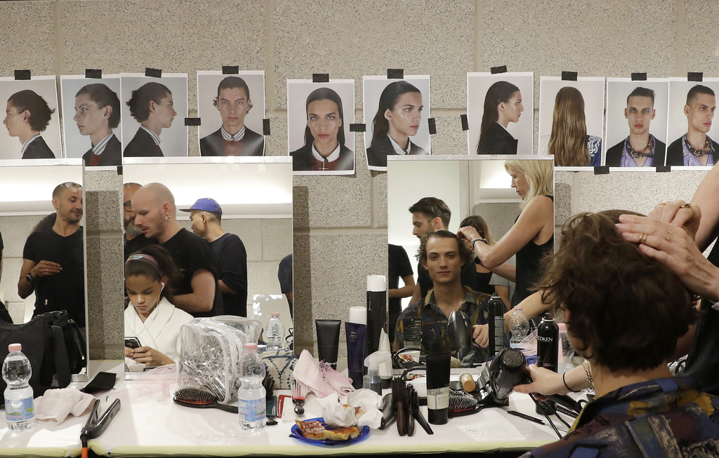 Models gets their hair done in the backstage prior to the presentation of the Versace men's Spring-Summer 2018 collection, part of the ...
