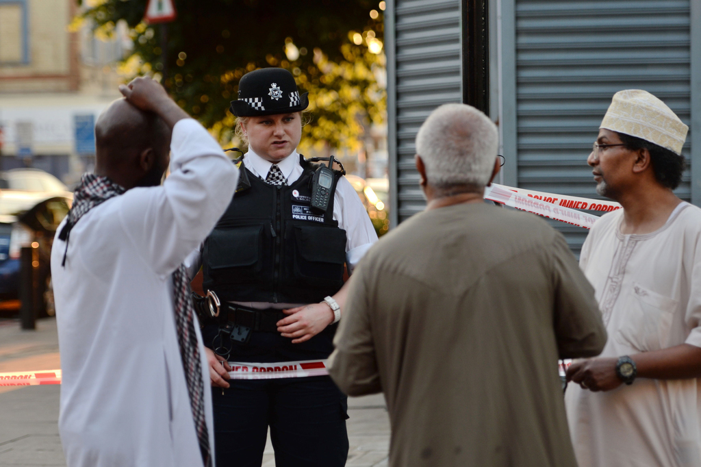 A police officer talks to local people at Finsbury Park in north London, where a vehicle struck pedestrians in north London Monday, Jun...