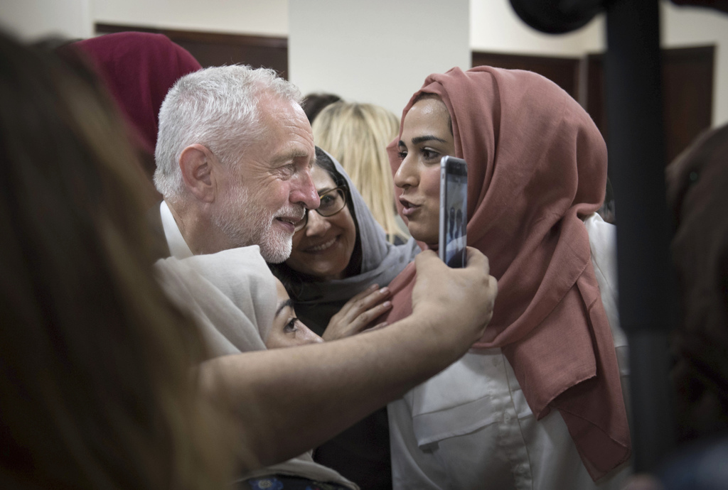Labour leader Jeremy Corbyn, left, meets locals at Finsbury Park Mosque in north London, after an incident where where a van struck ped...