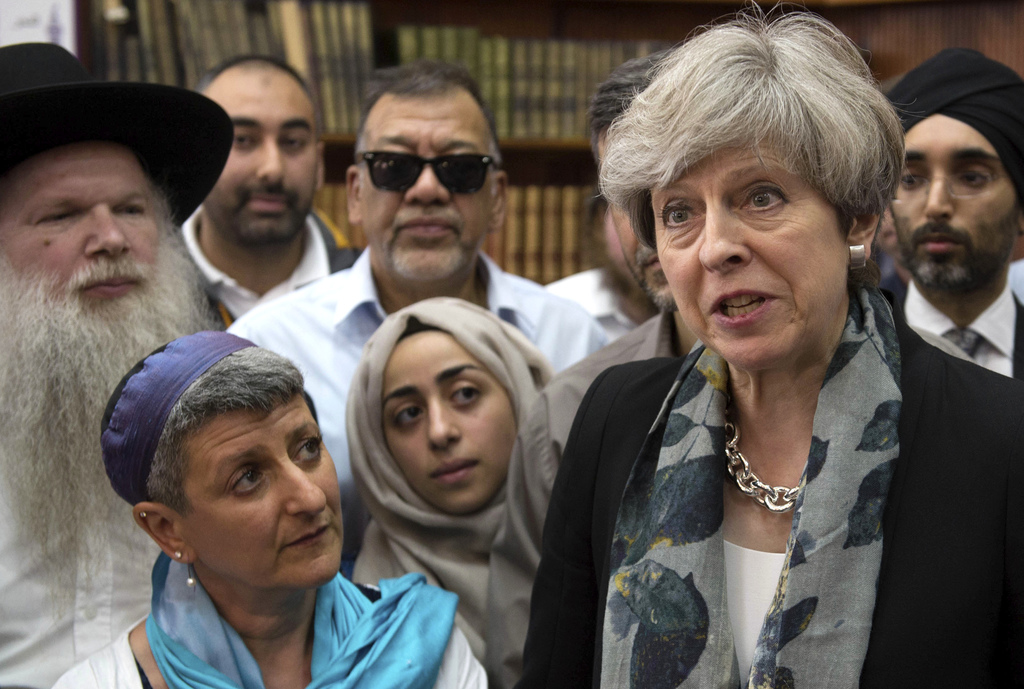 Britain's Prime Minister Theresa May, right, talk to faith leaders at Finsbury Park Mosque in north London, after an incident where whe...