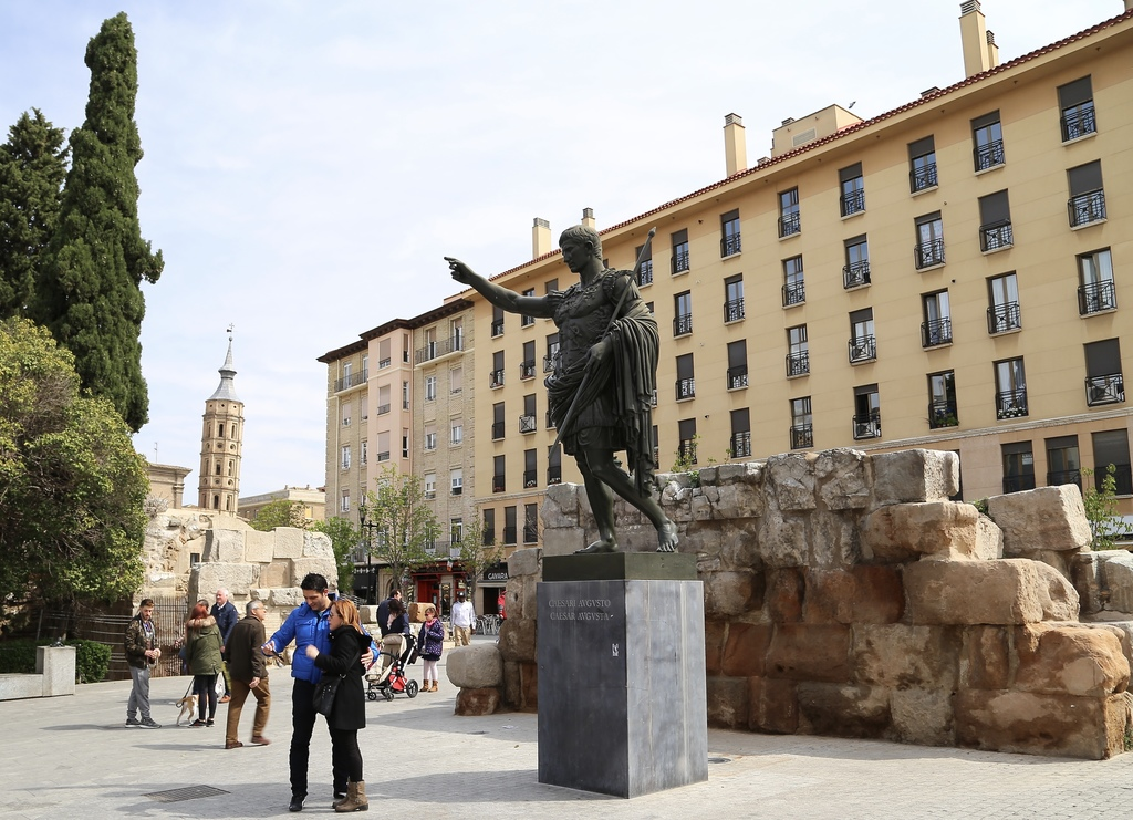 In this March 26, 2017 photo a couple takes a selfie in front of a statue of Caesar Augustus in Zaragoza, Spain. The city in Northeast ...