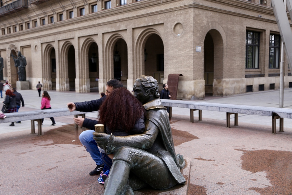 In this March 25, 2017 photo a couple takes a selfie in the arms of a sitting sculpture in Zaragoza, Spain's Plaza del Pilar. The huge ...