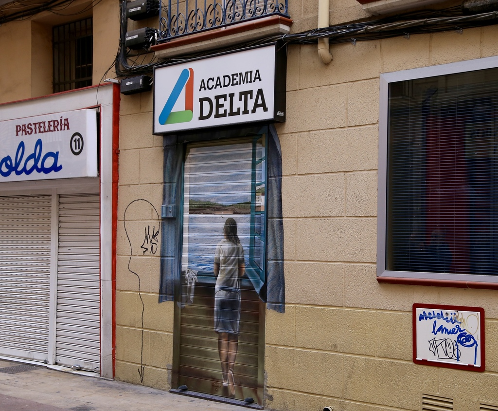 """This March 26, 2017 photo shows a painting in an unexpected place, a small, roll-up security gate on a doorway near the """"El Tubo"""" tapas..."""