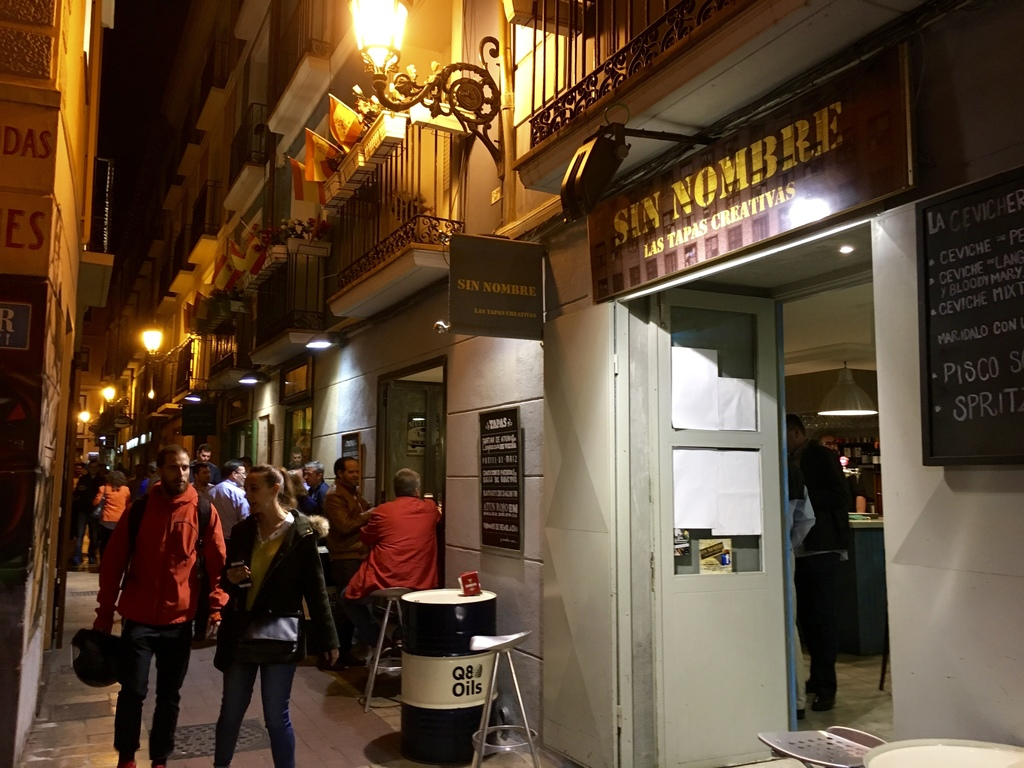 """This March 29, 2017 photo shows diners strolling """"El Tubo,"""" the narrow grid of alleys lined with tapas restaurants and bars in Zaragoza..."""