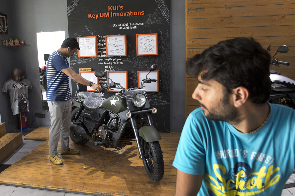 In this June 20, 2017 photo, a prospective buyer, left, looks at a Renegade commando motorcycle on display at the United Motors motorcy...