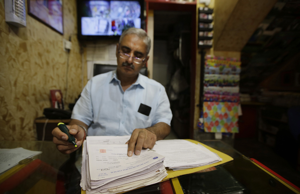 In this June 15, 2017 photo, Sanjiv Mehra, a toy shop owner checks his ledger at his shop in Khan Market, New Delhi, India. Indian busi...