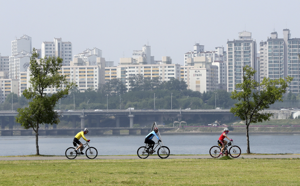 In this June 15, 2017 photo, people ride bicycles along the bike path of the Han river in Seoul, South Korea. In a country where bikes ...