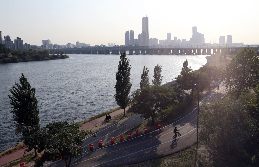 In this June 14, 2017 photo, a visitor rides a bicycle along the bike path of the Han river in Seoul, South Korea. In a country where b...