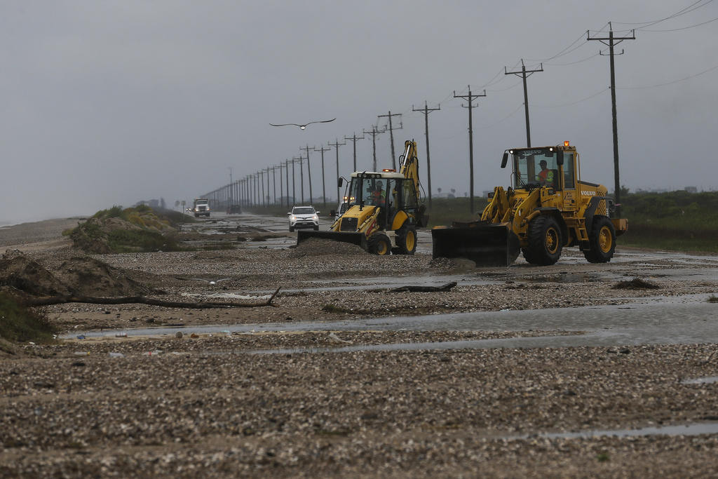 Crews work to clear sand and debris from State Highway 87 after Tropical Storm Cindy made landfall earlier Thursday, June 22, 2017 on t...