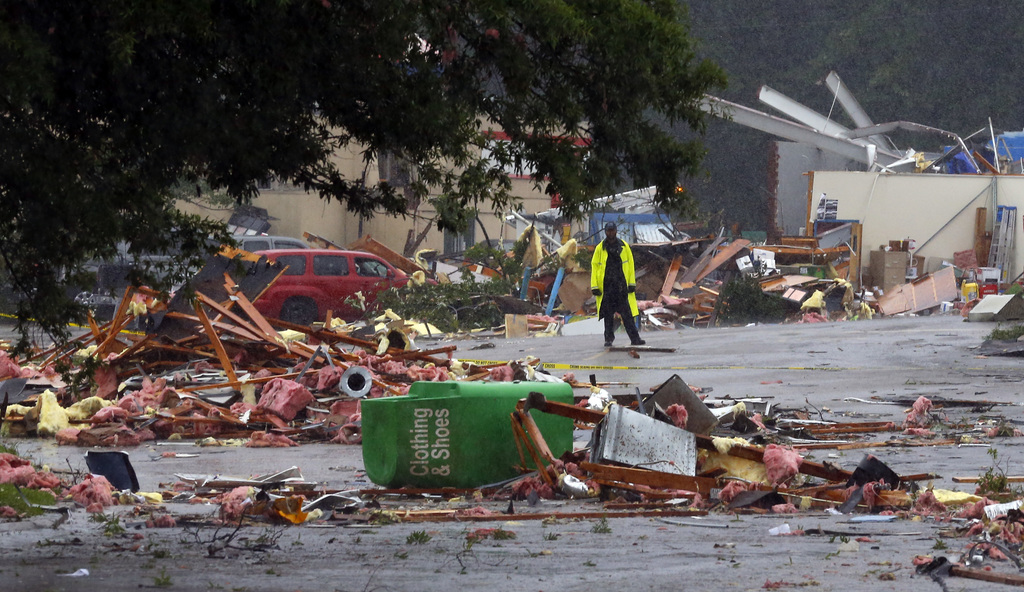 A police officer stands guard after a possible tornado touched down destroying several businesses, Thursday, June 22, 2017, in Fairfiel...