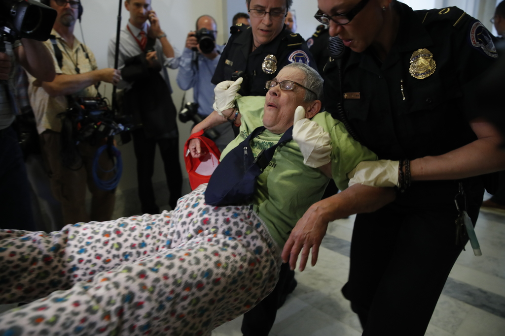 People are removed from a sit-in outside of Senate Majority Leader Mitch McConnell's office as they protest proposed cuts to Medicaid, ...