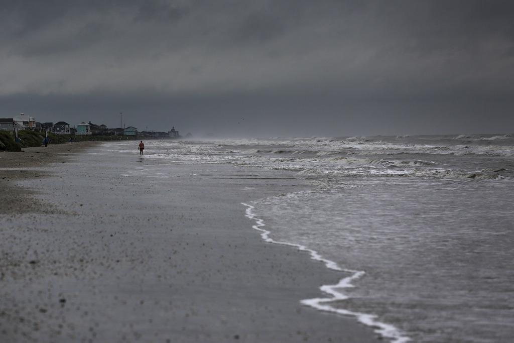A woman walks along the beach the morning after Tropical Storm Cindy made landfall Thursday, June 22, 2017, on the Bolivar Peninsula, T...