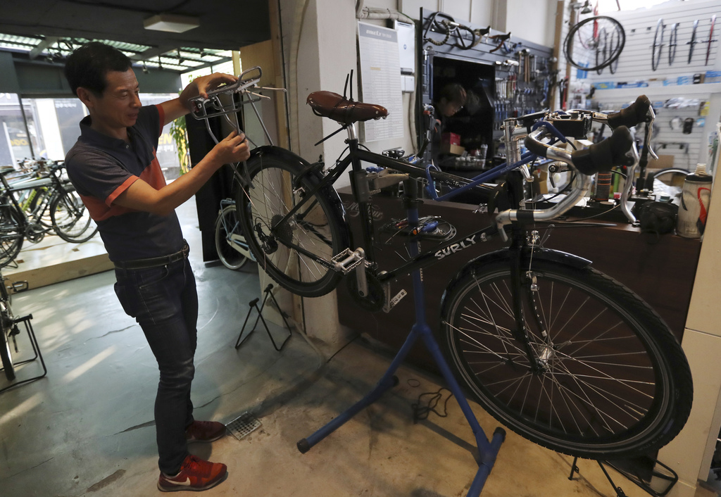 In this June 14, 2017 photo, Duk Young Lee explains about touring bike at his shop in Seoul, South Korea. In a country where bikes are ...