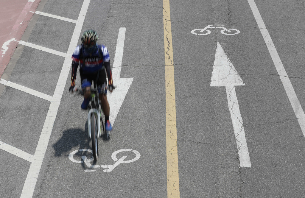 In this June 15, 2017 photo, a man rides a bicycle along the bike path in Seoul, South Korea. In a country where bikes are either a poo...