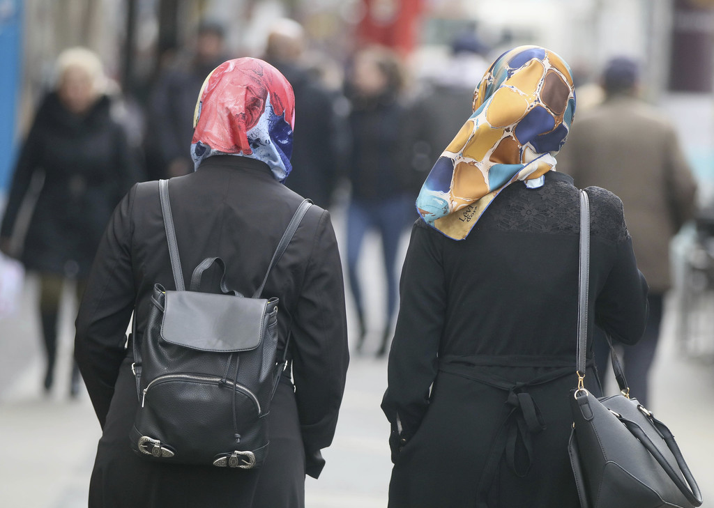 In this  April 21, 2017 photo women with head scarfs are walking in a pedestrian zone in Vienna, Austria.  An Austrian law banning dual...