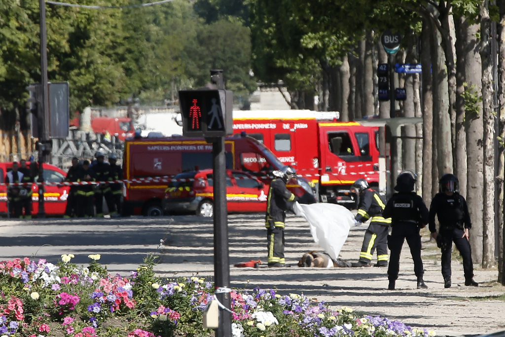 FILE - In this June 19 2017 file photo, rescue workers cover the dead body of an attacker on the Champs Elysees in Paris. The jihadis' ...
