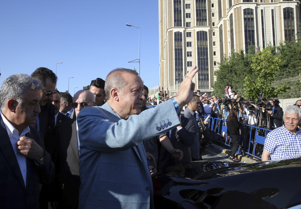 Turkey's President Recep Tayyip Erdogan waves toward his supporters after the Eid al-Fitr prayers in Istanbul, early Sunday, June 25, 2...