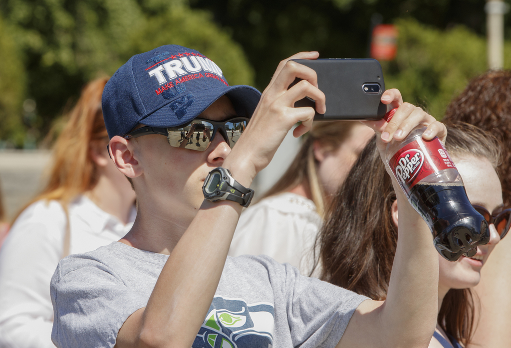Bryce Howard, 15, of Everett, Wash., wears a Trump hat as he snaps a photo during a visit to the Supreme Court in Washington, Monday, J...