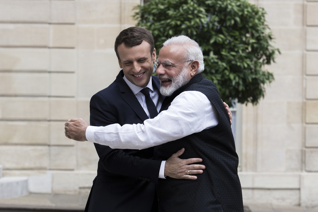 FILE - In this June 3, 2017, file photo, French President Emmanuel Macron, left, is hugged by Indian Prime Minister Narendra Modi befor...