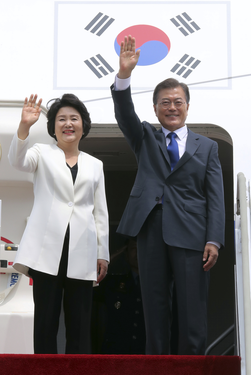 South Korean President Moon Jae-in and his wife Kim Jung-sook wave before leaving for the United States at the Seoul military airport i...