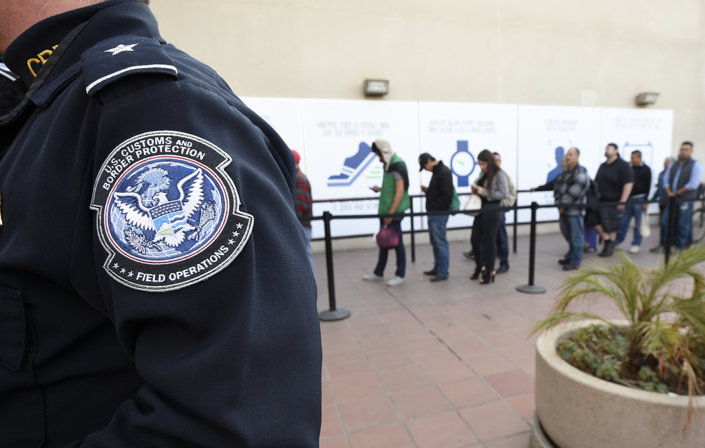 FILE - In this Dec. 10, 2015, file photo, pedestrians crossing from Mexico into the United States at the Otay Mesa Port of Entry wait i...