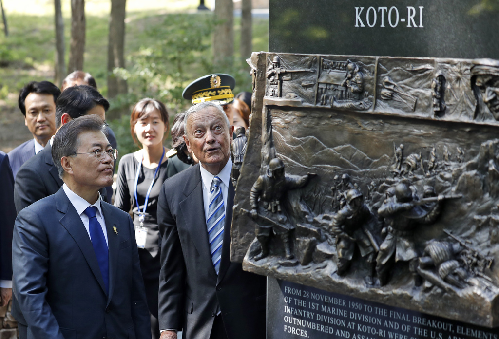 "South Korean President Moon Jae-in, left, walks around the ""Chosin Few Battle Monument,"" with former Marine Corps Lt. Gen. Stephen Olms..."