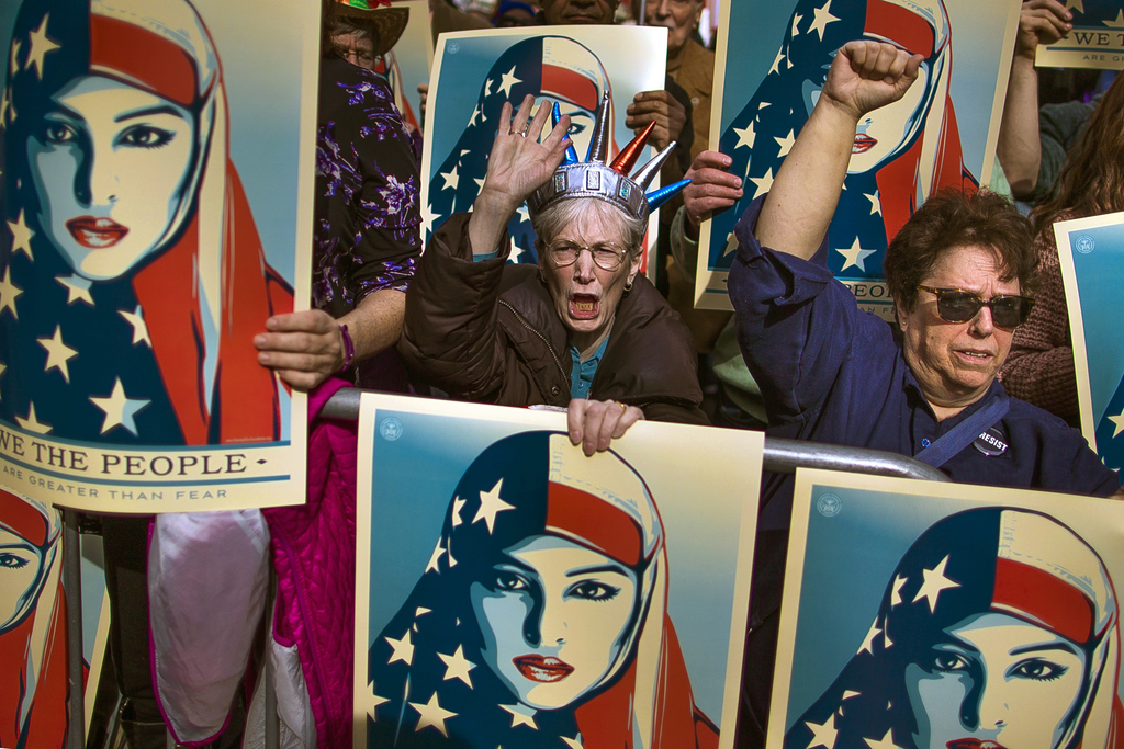 FILE - In this Feb. 19, 2017, file photo, people carry posters during a rally against President Donald Trump's executive order banning ...
