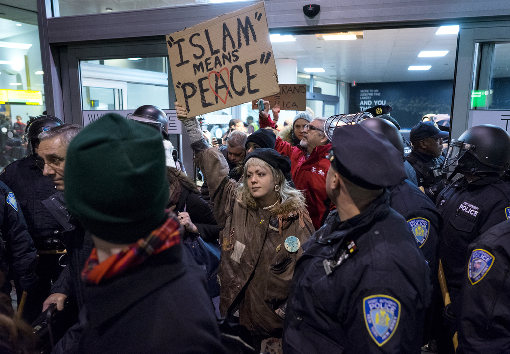 FILE - In this Jan. 28, 2017, file photo, protesters are surrounded by police officers and travelers as they pass through an exit of Te...