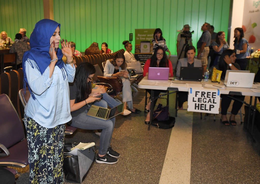 While activists and lawyers at the table at right offer help and information, Hanadi Al-Haj prays in the Tom Bradley International Term...