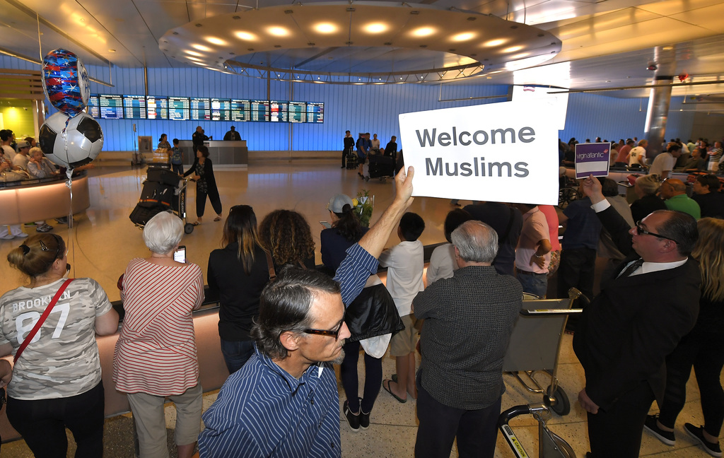 John Wider holds up a sign becoming Muslims in the Tom Bradley International Terminal at Los Angeles International Airport, Thursday, J...