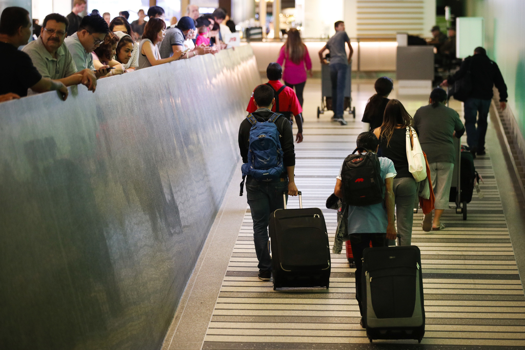 Travelers make their way up the arrival ramp at the Tom Bradley International Terminal at the Los Angeles International Airport Thursda...