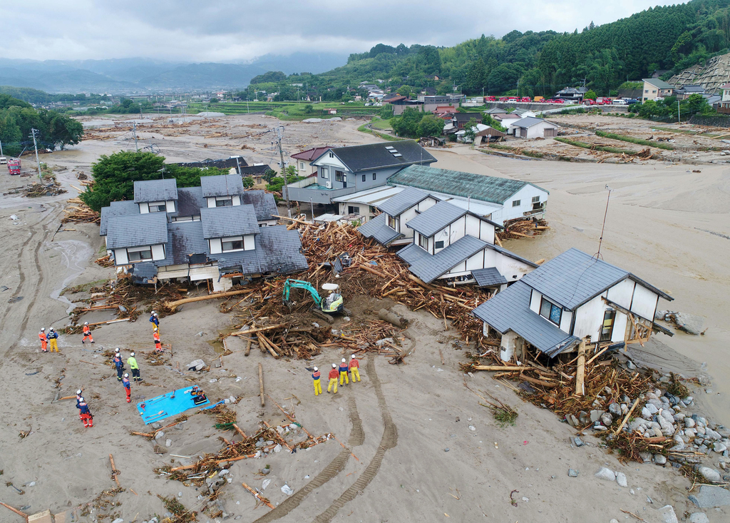Firefighters inspect the collapsed houses in the mud following the flooding caused by heavy rain in Asakura, Fukuoka prefecture, southw...