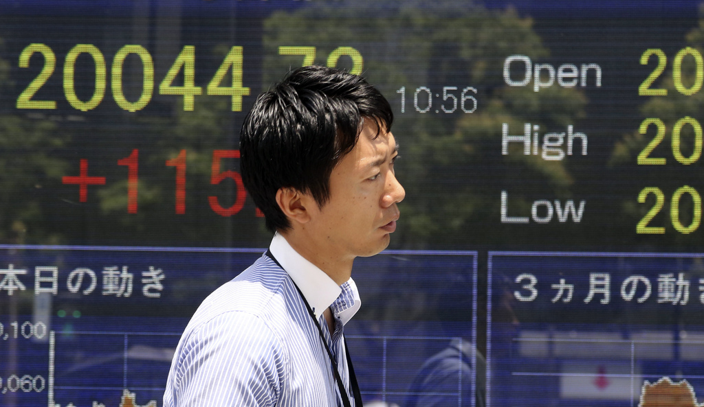 A man walks by an electronic stock board of a securities firm in Tokyo, Monday, July 10, 2017. Most Asian stock markets advanced Monday following Wall