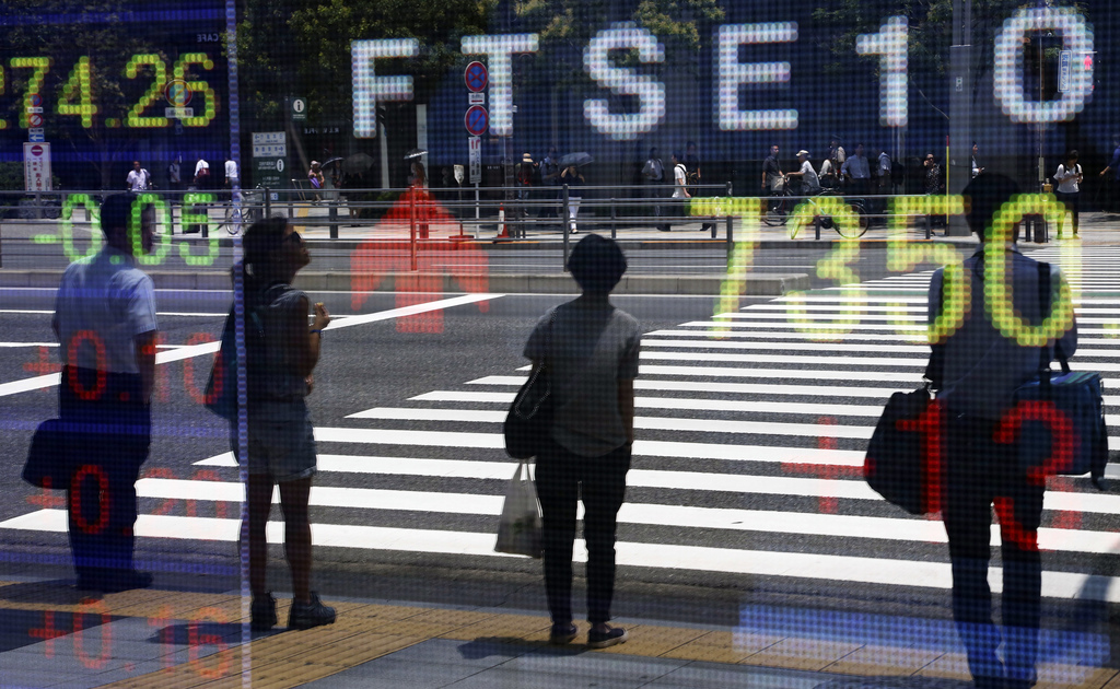 People are reflected on the electronic board of a securities firm in Tokyo, Monday, July 10, 2017. Most Asian stock markets advanced Monday following