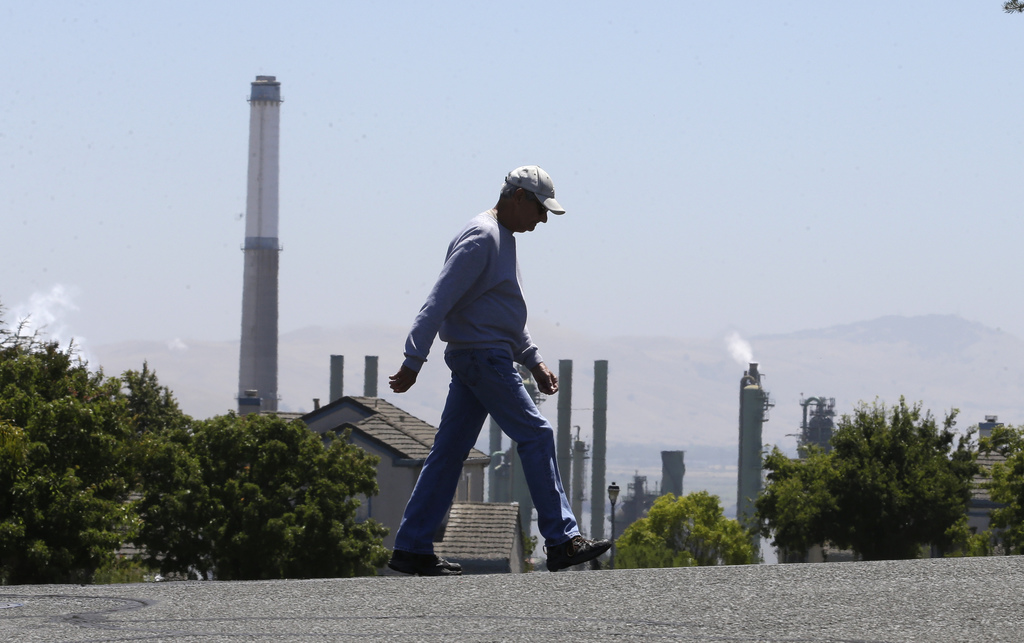 The stacks from the Valero Benicia Refinery are seen as a pedestrian walks in a nearby neighborhood, Wednesday, July 12, 2017, in Benicia, Calif. Cali...