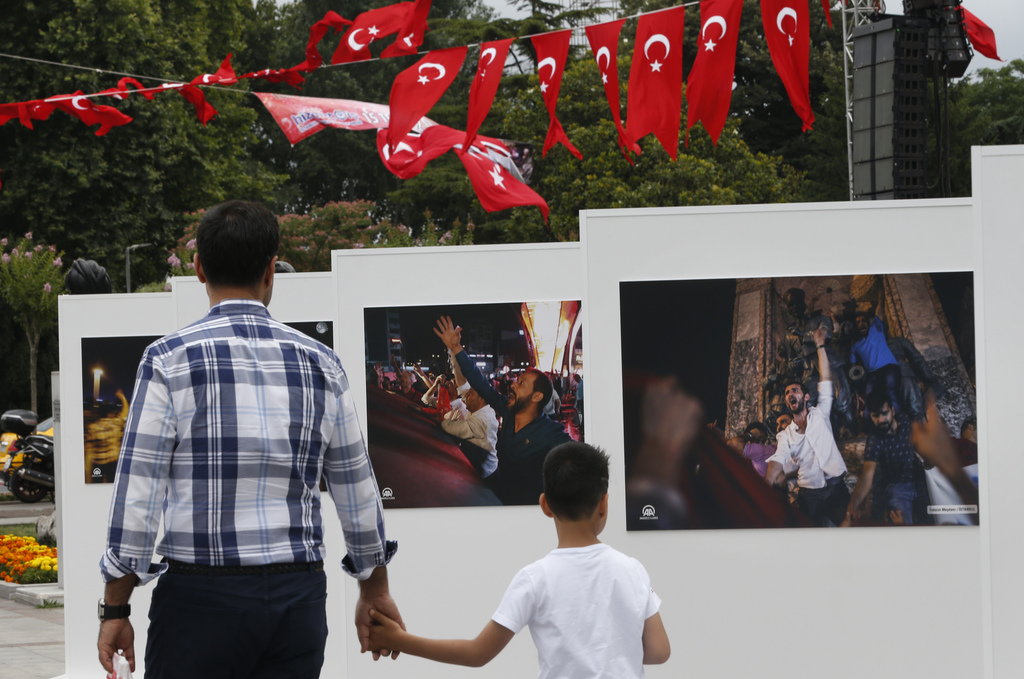 People visit an outdoor photo exhibition, featuring photographs of July 15, 2016 coup attempt, in Istanbul, Friday July 14, 2017. Turkey commemorates