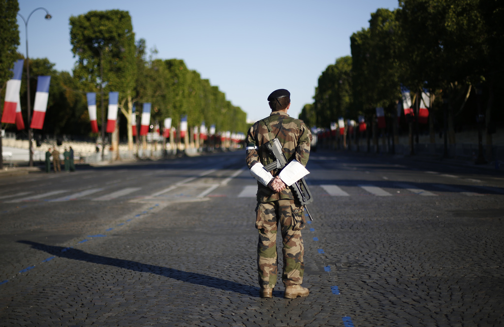 A French soldier waits on the Champs Elysees avenue before Bastille Day parade in Paris, Friday, July 14, 2017. U.S President Donald Trump and First L...