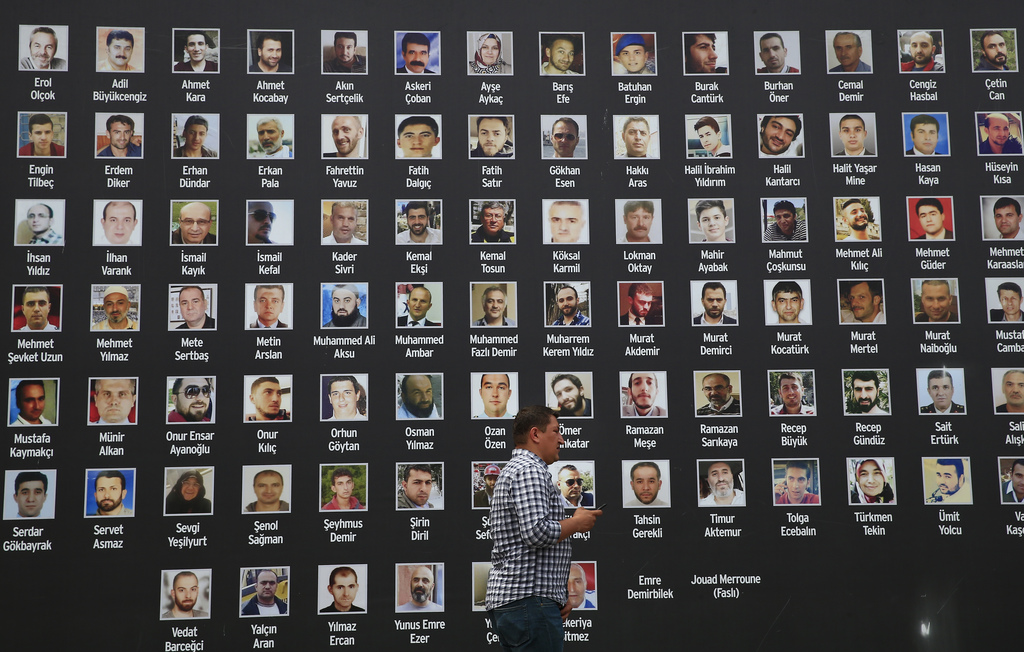 A man walk past a poster of photographs of victims of the July 15, 2016 coup attempt, in Istanbul, Friday July 14, 2017. Turkey commemorates the first