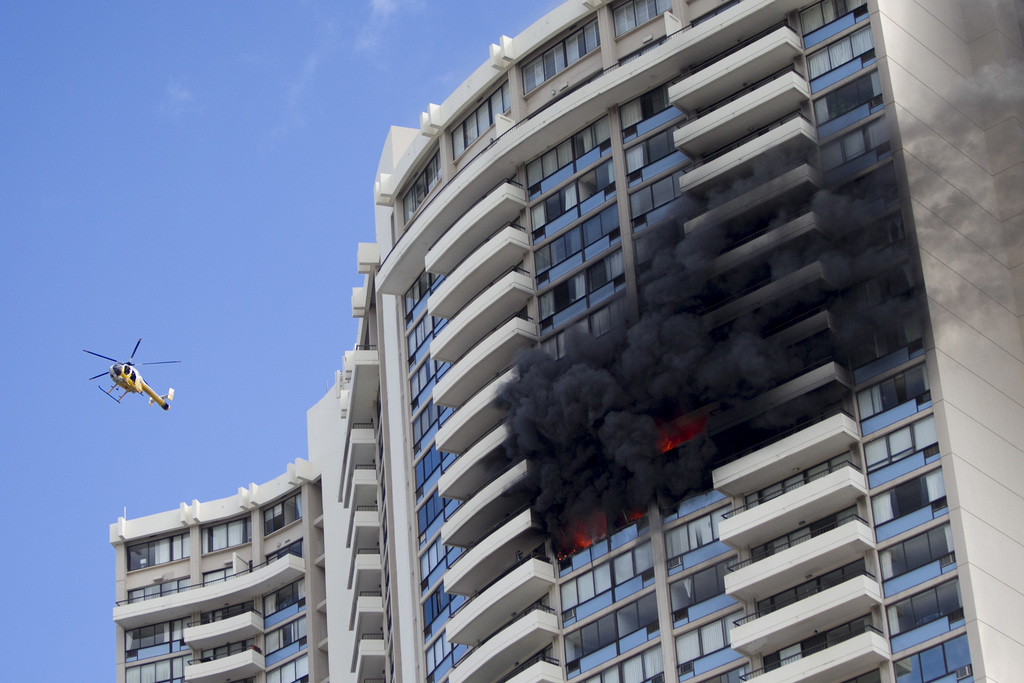 A Honolulu Fire Department helicopter flies near a fire burning on a floor at the Marco Polo apartment complex, Friday, July 14, 2017, in Honolulu. (A...