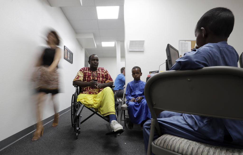 FILE - In this July 6, 2017, file photo, Ali Said, of Somalia, center, waits at a center for refugees with his two sons in San Diego. Said, whose leg ...