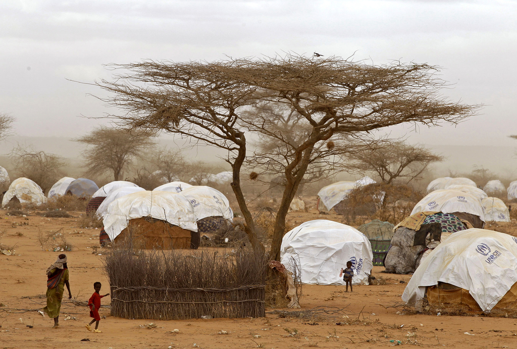 FILE - In this Aug. 4, 2011 file photo, refugees walk amongst huts at a refugee camp in Dadaab, Kenya. Earlier  in 2017, some Somali refugees whose re...