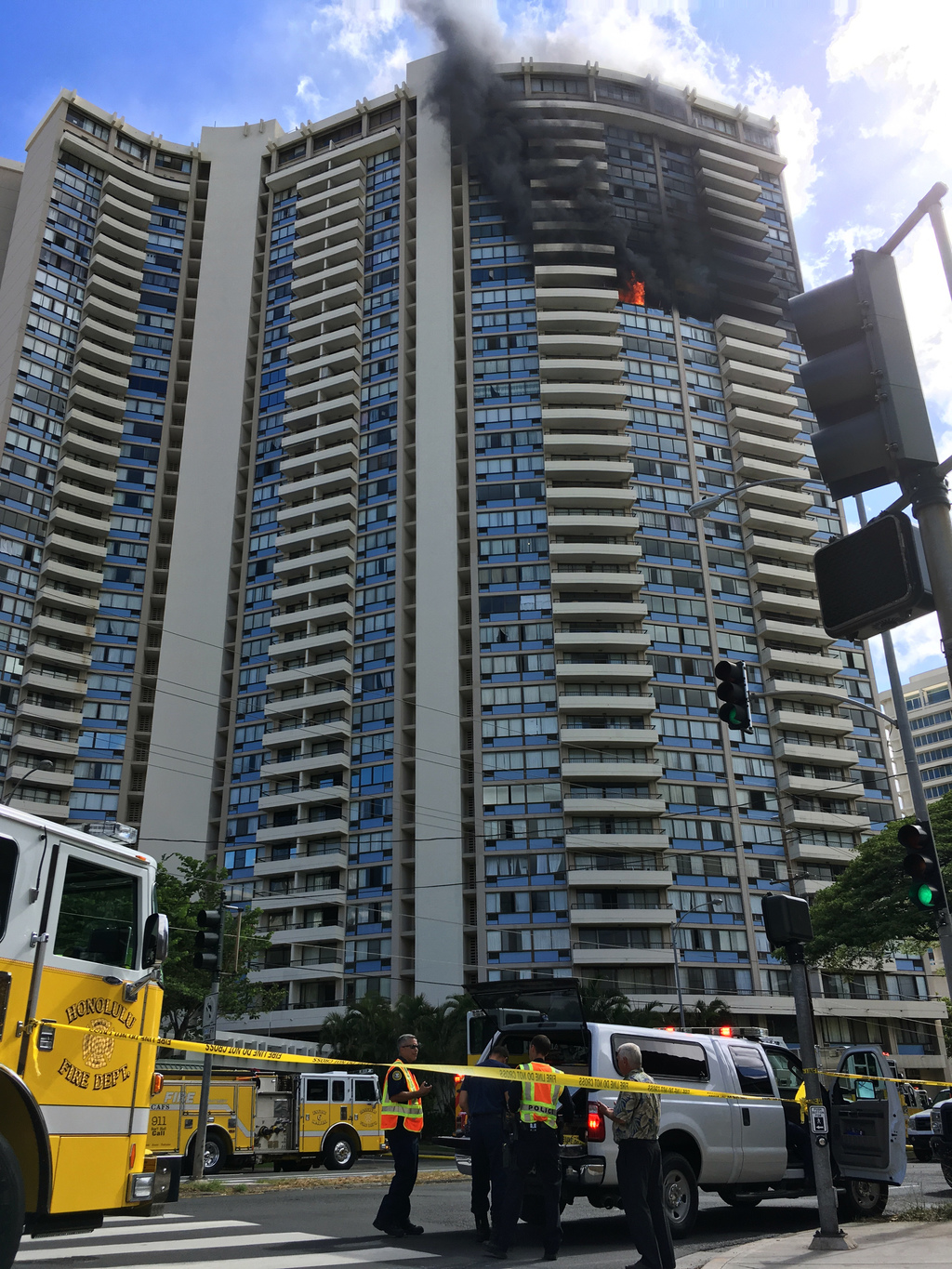 Law enforcement officers stand at the scene of a multi-alarm fire at the Marco Polo apartment complex in Honolulu, Friday, July 14, 2017. (AP Photo/Au...