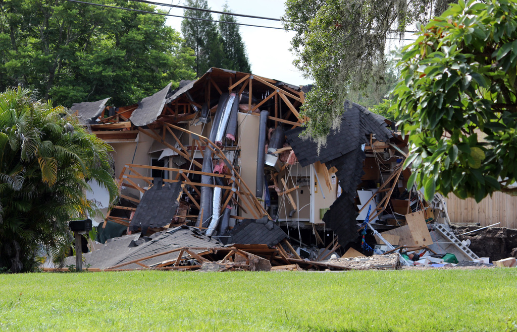 Debris is strewn about from a partially collapsed home in Land O' Lakes, Fla. on Friday, July 14, 2017.A sinkhole that started out the size of a small...