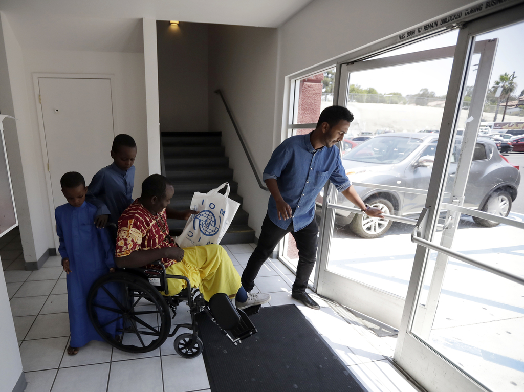 FILE - In this July 6, 2017, file photo, Ali Said, of Somalia, center, leaves a center for refugees with his two sons, as refugee caseworker Mohamed Y...